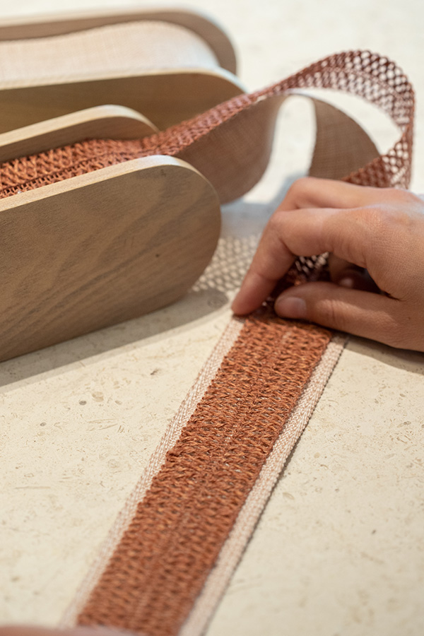 A solid tape can be seen between the open weave of a macrame border on top.