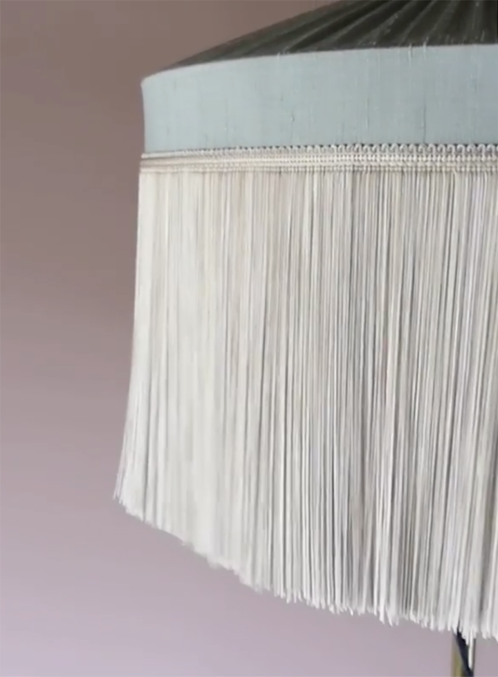 Long chainette fringe surrounds a silk lampshade.