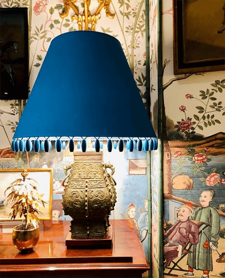 A bedside detail from a Miles Redd project, with a dark blue beaded fringe lampshade.