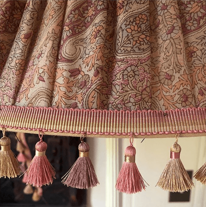Pink tassel fringe around a printed lampshade.