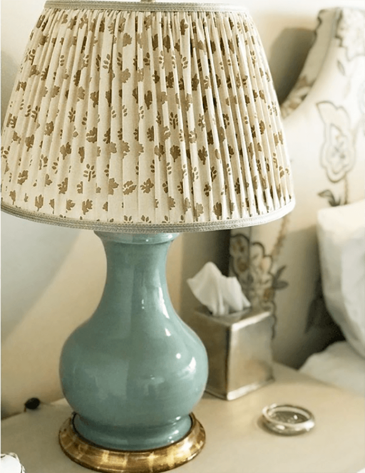 A pleated fabric lampshade on a bedside lamp.