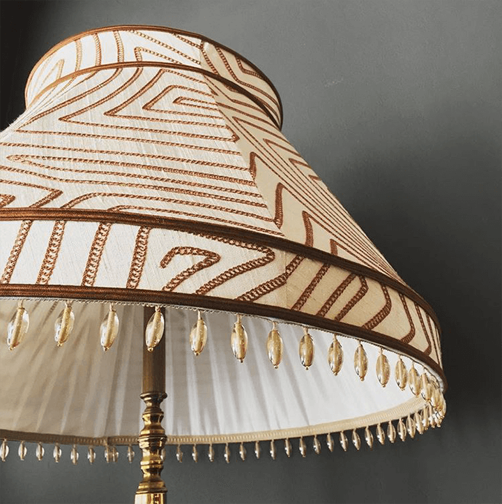 A fabric shade accented in gimp and beaded fringe.